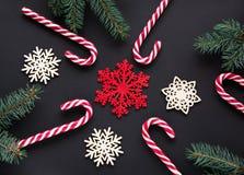 与银色丝带,绿色杉树,在黑背景的雪花的圣诞节糖果 抽象空白背景圣诞节黑暗的装饰设计模式红色的星形 顶视图 免版税库存照片