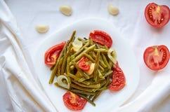 与银色叉子的被烘烤的菜在白色板材在烤箱烹调了:豆,土豆,葱 装饰用新鲜的蕃茄和大蒜 库存图片