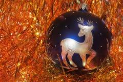 与银色图鹿的蓝色圣诞树装饰在红金黄闪亮金属片 图库摄影