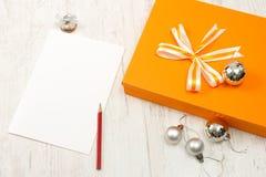 与银色圣诞节中看不中用的物品的橙色礼物盒 免版税库存图片