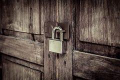 与银色挂锁的锁着的木门 免版税库存照片