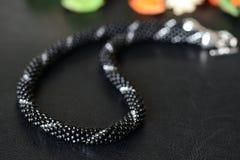 与银色线的黑串珠的项链在黑暗的背景 免版税库存照片