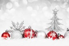 与银色装饰的圣诞节红色球在雪 免版税库存照片