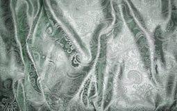 与银色金属挂毯的织品在淡绿色 免版税库存照片