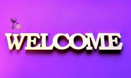 与银色首饰的白色欢迎在紫色梯度背景 免版税库存照片