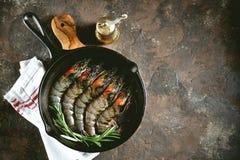 与铸铁煎锅的未加工的新鲜的老虎虾用新鲜的迷迭香和桃红色盐 食物健康海运 免版税库存照片