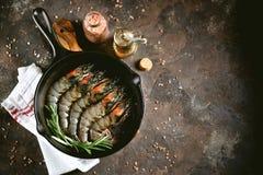 与铸铁煎锅的未加工的新鲜的老虎虾用新鲜的迷迭香和桃红色盐 食物健康海运 免版税库存图片