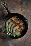 与铸铁煎锅的未加工的新鲜的老虎虾用新鲜的迷迭香和桃红色盐 食物健康海运 图库摄影
