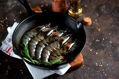与铸铁煎锅的未加工的新鲜的老虎虾用新鲜的迷迭香和桃红色盐 食物健康海运 库存图片