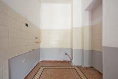 与铺磁砖的地板的空的厨房内部在恢复前 库存图片