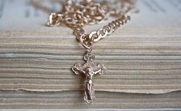 与链子的金十字架在一本旧书 免版税库存图片