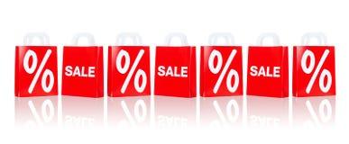 与销售和百分比的许多红色购物袋 免版税库存图片