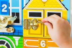 与锁的一场比赛 孩子打开锁 孩子的繁忙委员会 儿童` s教育玩具 免版税库存图片