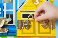与锁的一场比赛 孩子打开锁 孩子的繁忙委员会 儿童` s教育玩具 免版税库存照片