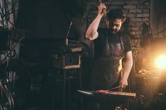 与锤子的铁匠运作的金属在伪造的铁砧 库存照片