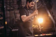 与锤子的铁匠运作的金属在伪造的铁砧 免版税图库摄影