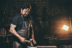 与锤子的铁匠运作的金属在伪造的铁砧 免版税库存图片