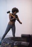 与锤子的黑人妇女锻炼和拖拉机疲倦 免版税库存照片