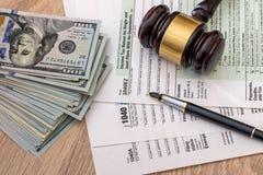 1040与锤子金钱,笔的报税表 免版税库存图片