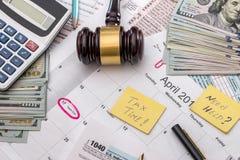1040与锤子金钱,笔的报税表 图库摄影