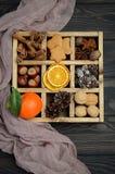 与锥体、姜饼曲奇饼、坚果、香料和干桔子的圣诞节背景 免版税库存图片