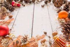 与锥体、杉木吠声、橡子和玩具的抽象圣诞节框架 背景空白木 免版税库存照片