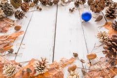 与锥体、杉木吠声、橡子和玩具的抽象圣诞节框架 背景空白木 库存照片