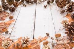 与锥体、杉木吠声、橡子和玩具的抽象圣诞节框架 背景空白木 免版税图库摄影