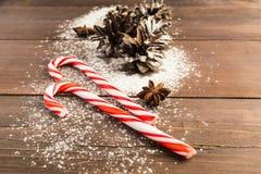 与锥体的圣诞节棒棒糖在木背景 免版税图库摄影
