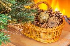 与锥体的圣诞节篮子在壁炉附近 免版税库存照片