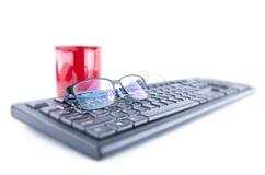 与键盘和咖啡杯的眼睛玻璃 库存照片