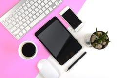 与键盘的办公室桌,老鼠、笔记本、数字式片剂和智能手机在现代两定调子白色和桃红色背景 免版税库存图片