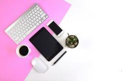 与键盘的办公室桌,老鼠、笔记本、数字式片剂和智能手机在现代两定调子白色和桃红色背景 库存照片
