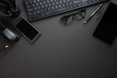 与键盘的办公用品在灰色书桌上 免版税库存图片