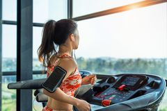 与锻炼机器的年轻女人锻炼在健身房 免版税库存照片