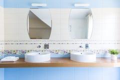 与镜子的两个水槽在最低纲领派卫生间里 免版税库存照片