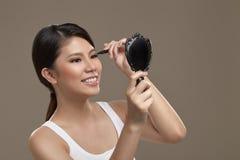 与镜子的女性亚洲申请的眼睛划线员 免版税库存照片