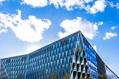 与镜子的现代建筑学大厦 与云彩的天空在Th 免版税库存照片