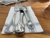 与镶边餐巾的叉子刀子颠倒的匙子银器餐位餐具 免版税库存照片