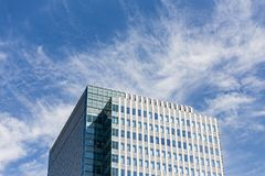 与长方形和正方形窗口的现代大厦facede形成与与云彩的清楚的蓝天在札幌在北海道 免版税图库摄影