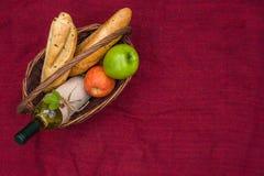 与长方形宝石、苹果和瓶的野餐篮子白葡萄酒wi 免版税库存照片