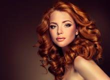 与长的卷曲红色头发的女孩模型 库存照片