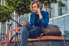 与长的头发的一个英俊的时兴的有胡子的男性坐与自行车的一条长凳,与片剂计算机一起使用和 库存照片