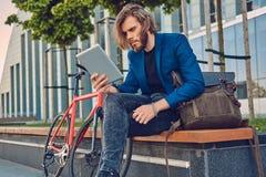 与长的头发的一个英俊的时兴的有胡子的男性坐与自行车的一条长凳,使用片剂计算机 库存照片