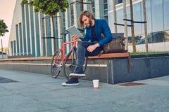 与长的头发的一个英俊的时兴的有胡子的男性坐与自行车的一条长凳,使用片剂计算机 免版税库存图片