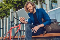 与长的头发的一个英俊的时兴的有胡子的男性坐与自行车的一条长凳,使用片剂计算机 库存图片