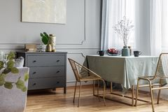 与长的桌、时髦的金黄椅子和灰色木洗脸台的餐厅内部 库存照片