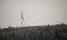 与长的缆绳导线的高压塔在日落时间天空的一座山 免版税库存照片
