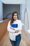 与长的黑发的妇女模型在白色站立在大厅里的衬衣和蓝色牛仔裤在拿着笔记本的学院大学 免版税库存照片