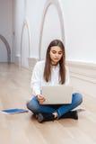与长的黑发的妇女模型在白色衬衣和蓝色牛仔裤坐地板在大厅里在研究膝上型计算机的学院大学 免版税库存照片